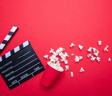 Cinema film concept. Fresh salty pop corn and movie clapper board, red color background, top view